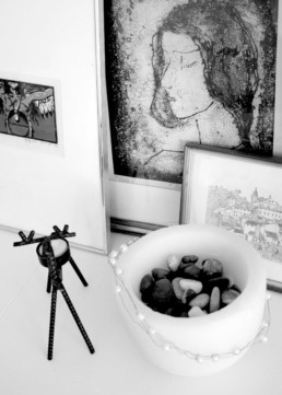 bw picture of several framed artworks behind a metal reindeer candleholder and a bowl with natural stones in it