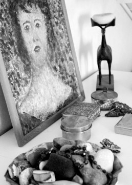 bw picture of small metal cases and other ornaments beside a framed portrait oil painting.