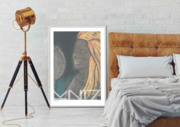 Picture of a bedroom with a lamp and a large framed art print beside the bed