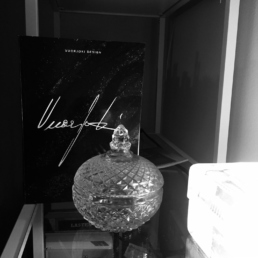 bw picture of a glass ornament with an artwork catalog behind it