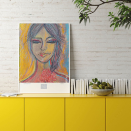 Picture of a yellow cabinet with a framed colorful art print and books on top