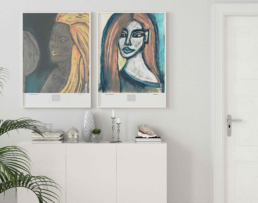 Picture of a white living room cabinet with two framed art prints on the wall