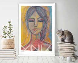 Picture of books and a cat beside a large framed colorful art print