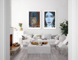 Picture of a white living room with a fireplace and two colorful art prints on the wall