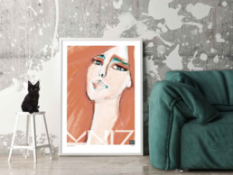 Picture of a green sofa and a black kitten with a large red art print