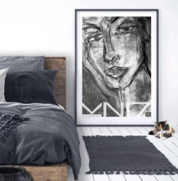 Picture of a bedroom with a large framed art print and a kitten