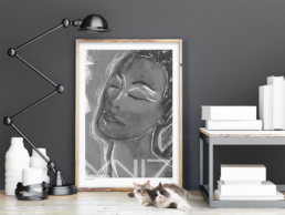 Picture of two cats in front of a framed art print portraying a woman