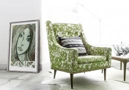 Green portrait art print beside an armchair with green flower pattern