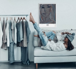 Young woman on the sofa with portrait art print on the wall and a rack of clothes
