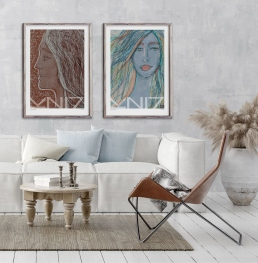 Boho style livingroom with white sofa with pillows, a leather chair, a large ceramic pot with feathers and two large framed portrait art posters on the wall