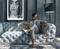 Stylish man having luxurious lifestyle, sitting on the sofa with portrait art print on the wall.