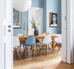 Portrait art prints on a blue dining room wall